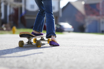 Low section of girl skateboarding on street