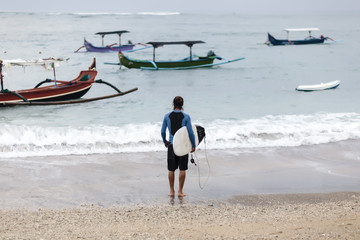 Rear view of man looking at sea while carrying surfboard on shore
