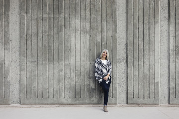Woman leaning on wall while standing on footpath