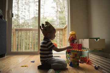 Side view of boy playing with toy blocks at home
