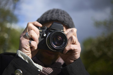 Close-up of man photographing with DSLR camera