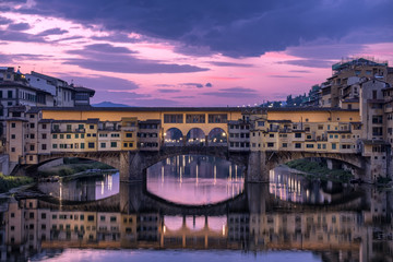 Ponte Vecchio over River Arno against sky at dusk