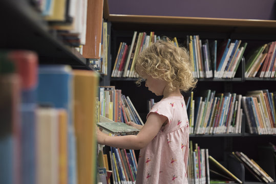 Side view of girl looking at book while standing in library