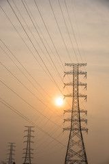 Group silhouette of transmission towers (power, electricity pylon, steel lattice) at sunset in suburb area of Hanoi, Vietnam. Texture high voltage pillar, overhead power line, industrial background.