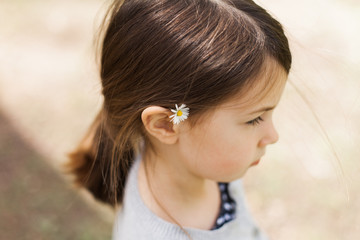 Profile of pretty little girl with small daisy tucked behind her ear