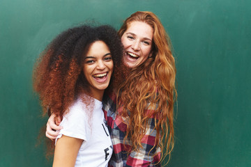 Portrait of two girlfriends laughing against of green background
