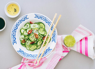 Fototapeta Thai salad of cucumber, dressing for salad, ricin vinegar, spices, bright cloth. Top view