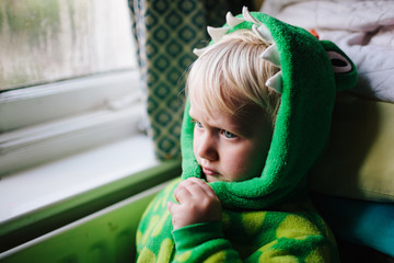 A little child dressed as a dragon taking some time out.