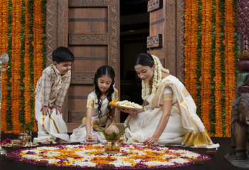 South Indian woman making a flower rangoli with son and daughter