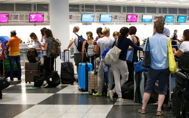 People queue to check in at Munich airport