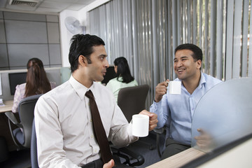 Two male executives having tea in office