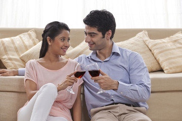 Young couple toasting wine at home