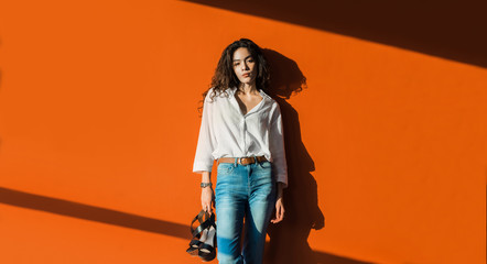 Portrait of beautiful fashionable mixed woman with orange wall in background.