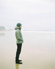 Man standing on a beach on a foggy winter day looking out to sea