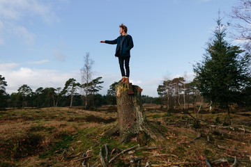 Young leader standing on tree stump pointing in a direction