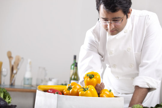 Chef inspecting yellow bell peppers