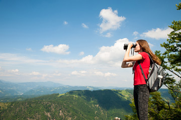 active Young woman looking a mountain landscape with Binoculars