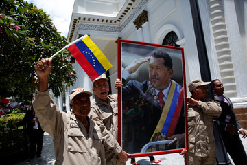 Members of the militia carry a picture of Venezuela's late President Hugo Chavez outside Palacio Federal Legislativo during the National Constituent Assembly's first session, in Caracas