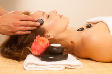 attractive young beautiful woman having facial massage with mineral stone