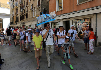 A group of tourists follows a guide near St.Mark's square in Venice