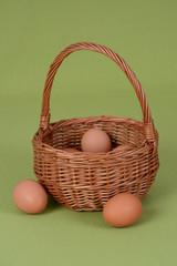 Kurze jajka w wiklinowym koszyku na zielonym obrusie
