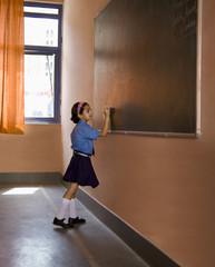 School girl writing on the black board