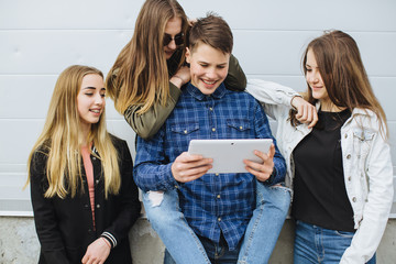 Group of teenagers sitting outdoors using their tablet.
