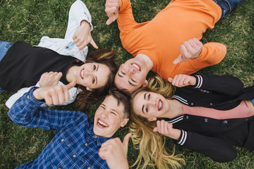 Teenagers lie on the grass after school.
