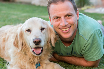 Man with his Golden Retriever dog laying on grass outdoors looking at camera smiling.