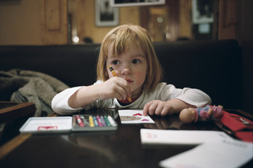 Young Girl Concentrating, Drawing With Crayon At Table