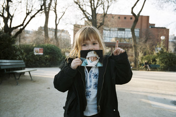 Young Girl Holding Photo Of Herself As Baby