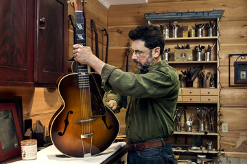 Middle aged man working on a guitar in a restoration shop