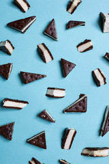 Triangularly cut ice cream sandwich pieces lay against a bright blue background.