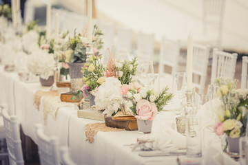 floral decoration on a wedding, white table with vintage wooden chairs, vintage books and lace