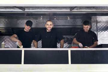 Cheerful group of chefs cutting vegetables inside food truck