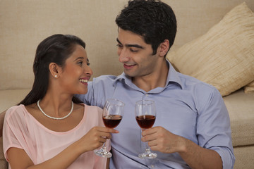 Smiling young couple holding wineglass while looking at each other