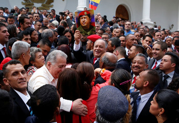 Diosdado Cabello, member of the National Constituent Assembly, holds a picture of late Venezuela's President Hugo Chavez after posing for a family picture during the first session of the assembly at Palacio Federal Legislativo in Caracas