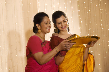 Mother and daughter with a tray of diyas
