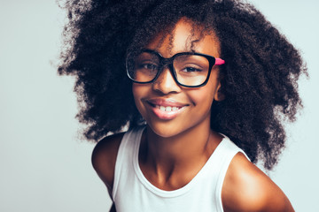 Cute little African girl wearing glasses against a gray backgrou