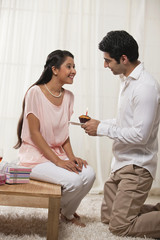 Handsome young man kneeling while giving cupcake to woman at home