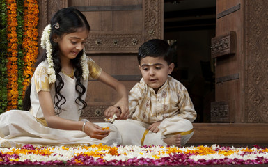 South Indian girl helping her brother with a rangoli