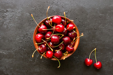 Fresh cherry in a plate on a black background