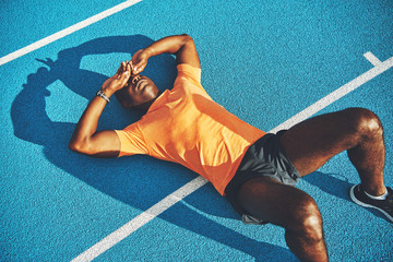 Tired young athletic lying on a running track after training Wall mural