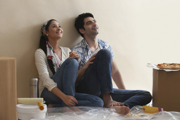 Smiling young couple leaning against the wall while thinking
