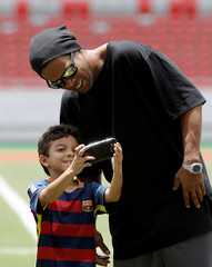 A boys takes a picture with Brazilian soccer star Ronaldinho at the National Stadium in San Jose, Costa Rica