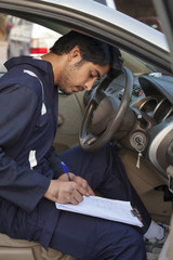 Mechanic examining car and writing on clipboard