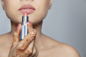 Close-up of a woman applying lipstick