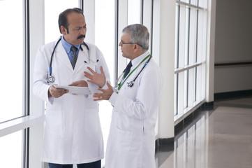 Two doctors talking in corridor of hospital