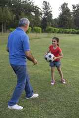 Grandfather and granddaughter playing with a football