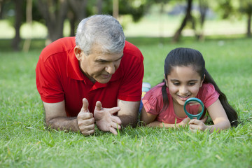 Grandfather teaching his granddaughter to use magnifying glass